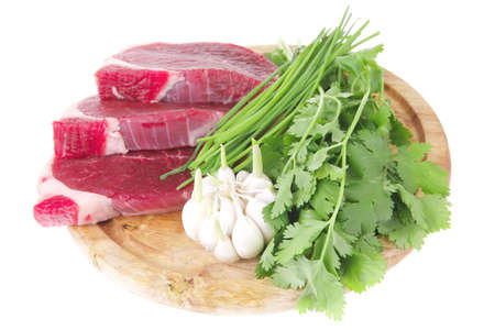 fresh meat : raw uncooked fat lamb pork fillet with green stuff and garlic on wooden plate isolated over white background photo