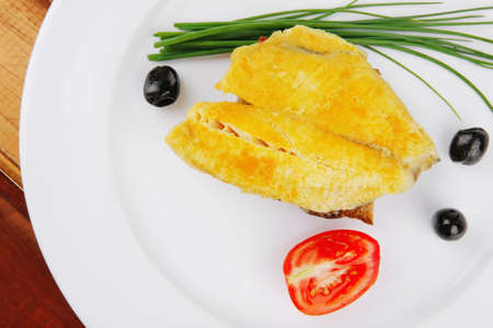 savory: fish fillet served on plate over wood with tomatoes,olives and bread  Stock Photo - 10272083