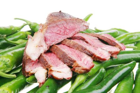 고기의: meaty food : roast meat steak sliced over green hot chili peppers on a white background