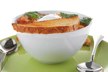 red tomato soup with toasts on green plate photo