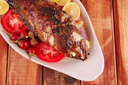 main course: whole fryed sunfish on wooden table with lemons and peppers Stock Photo - 10309141