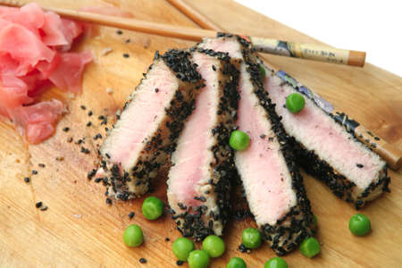 roast tuna sliced on wooden plate with green peas and chopsticks over white photo