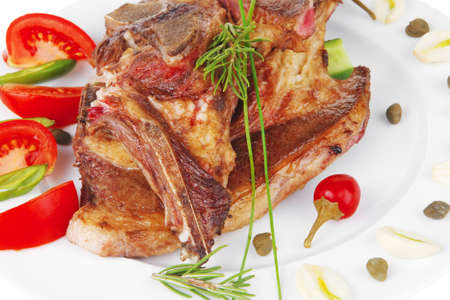 fresh roasted beef meat bone steak on ceramic dish with red hot pepper and tomatoes isolated  over white background photo