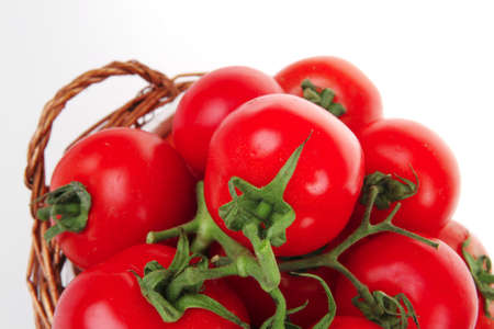 fresh tomatoes on green branch in wicker basket isolated on white background  photo