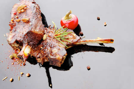 savory plate: grilled ribs over black with spices and hot pepper photo