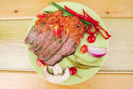 beef slices on plate over wooden table photo
