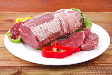 raw uncooked meat on wooden table with vegetables photo