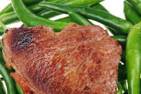 고기의: meaty food : grilled red meat steak over green hot chili peppers on a white back background