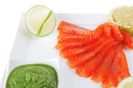 salmon ahumado: salmón ahumado y salsa verde sobre fondo blanco Foto de archivo