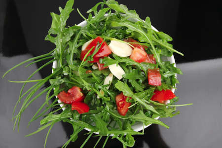 healthy appetizer : salad with raw tomato , garlic , and green staff in white bowl on black background photo