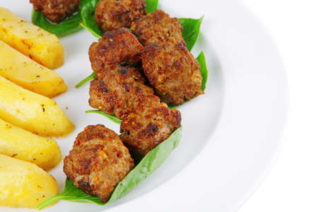 served meatballs on basil leaf with gold potatoes photo