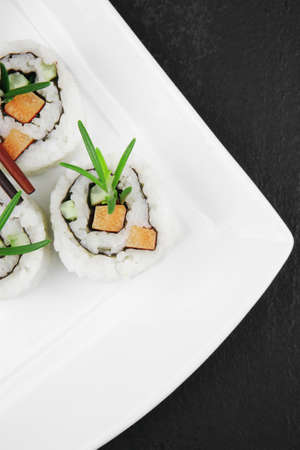 Maki Sushi - California Roll with Cucumber , Cream Cheese and Salmon inside. Served with wasabi and ginger . on long white plate over black table Stock Photo - 10454491