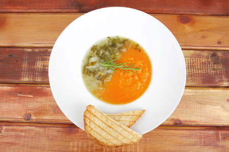 european cuisine: dual components vegetable soup with toasts over wood photo