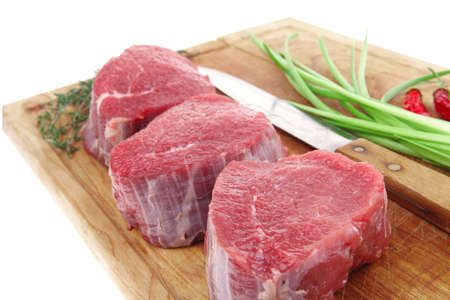 raw fillet chops : fresh beef meat with thyme and red hot dry pepper on wooden plate . isolated over white background Stock Photo - 10478175