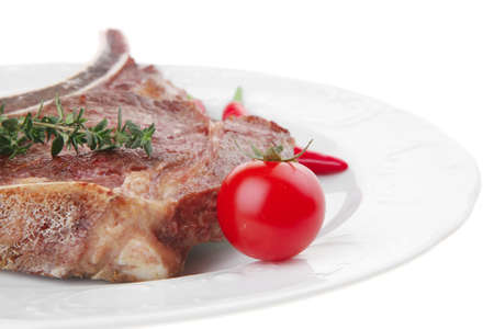 meat food : grilled beef spare rib on white dish with thyme pepper and tomato isolated over white background photo