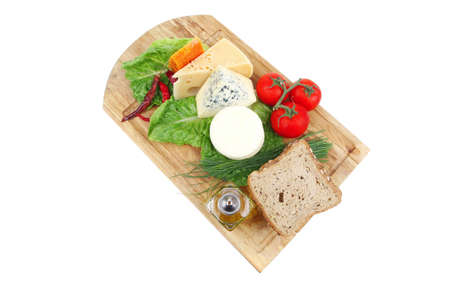 roquefort with cheddar, parmesan and soft feta cheese on wooden board with tomatoes bread and olive oil isolated over white background photo
