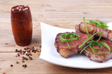 human meat: grilled meat beef steaks strips on white plate with pepper and cutlery over wood table
