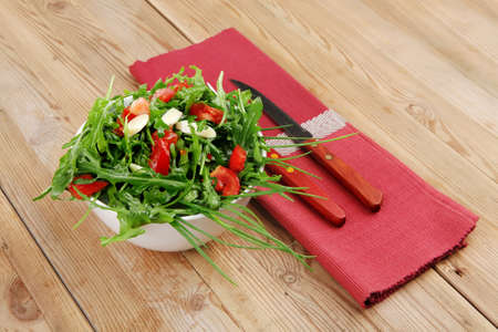 healthy appetizer : salad with raw tomato , garlic , and green staff in white bowl over wood served with cutlery photo