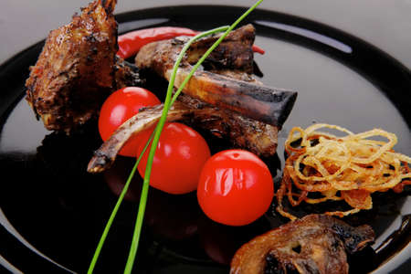 ribs on black with pepper and cherry tomatoes photo