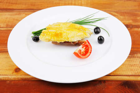 roasted fish fillet with tomatoes,chives and bread on plate over wooden table Stock Photo - 10590817