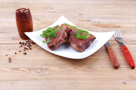 roasted beef meat strips steak on white ceramic plate with hot dry pepper on wood table photo