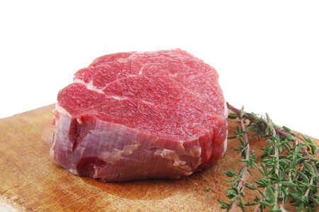 raw steak: red fresh fillet chops : raw beef fillet on wooden board with thyme ready to prepare . isolated over white background Stock Photo