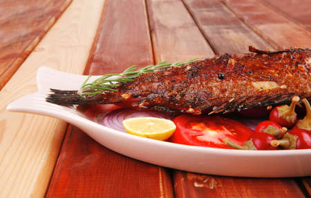 main course: whole fryed sunfish on wooden table with lemons and peppers photo