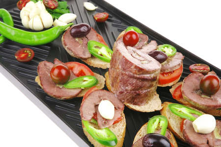 snakes on black grill plate : tartlets with sliced meat isolated over white background photo