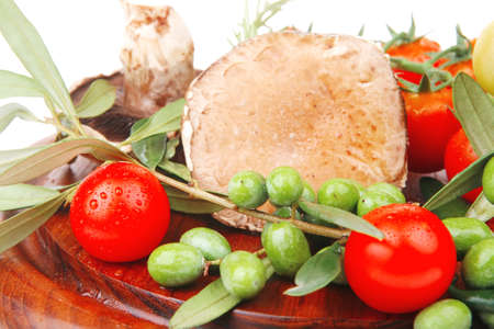 vegetables and olives over wooden plate on white photo