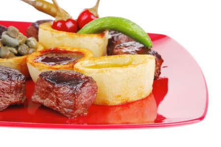 european food: europeo de alimentos: la carne de vacuno a la parrilla en plato de porcelana de color rojo sobre fondo blanco con alcaparras y salsa de barbacoa