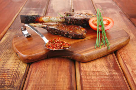 meat savory on wooden plate: roast ribs with peppers tomato and dry spices over wooden table photo