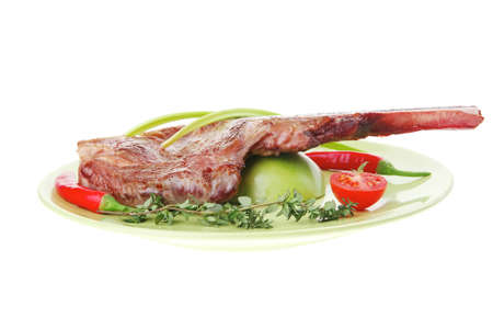 meat food : roast rib on green dish with thyme pepper and tomato isolated over white background photo