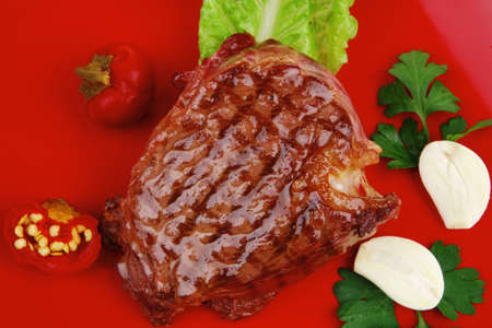 meat savory : beef grilled and garnished with green lettuce and red chili hot pepper on red plate isolated over white background photo