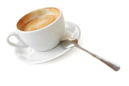 sweet drink : small white cup of cappuccino coffee on light background with spoon photo