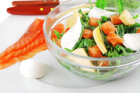 green salad with smoked salmon and bread in transparent bowl photo