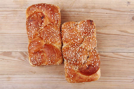 hot bun of light wheat bread topped by sesame seeds on wood photo