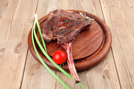 meat savory : grilled beef ribs served with green chives and cherry tomato over wood Stock Photo - 10698186