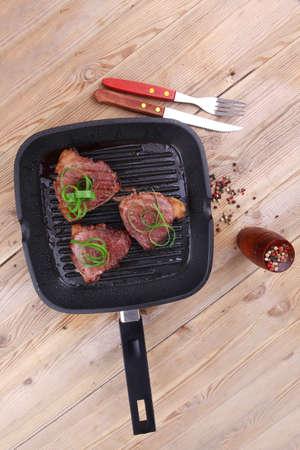 roast bloody beef fillet steaks on black grill plate on wood photo