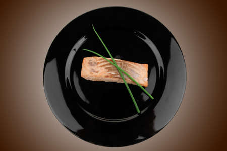 savory fish portion : norwegian salmon fillet roasted with green chinese onion, on black dish isolated over white background Stock Photo - 10706371