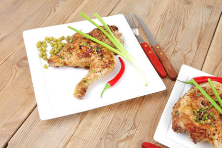 roast chicken : legs garnished with green peas , peppers , and cutlery on white plates over wooden table Stock Photo - 10712954