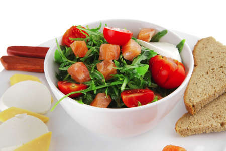 fresh green salad with smoked salmon in white bowl photo