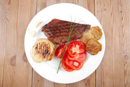 meat food : roast beef fillet mignon served on white plate with tomatoes , potatoes , and chives on wooden table photo