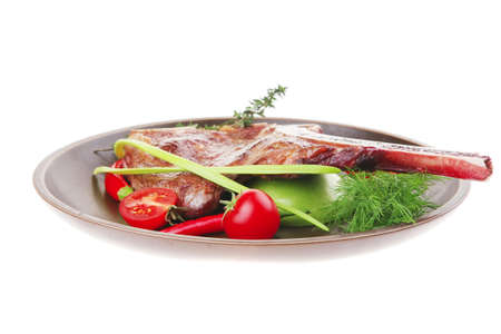 lean back: meat food : roast rib on dark dish with thyme pepper and tomato isolated over white background