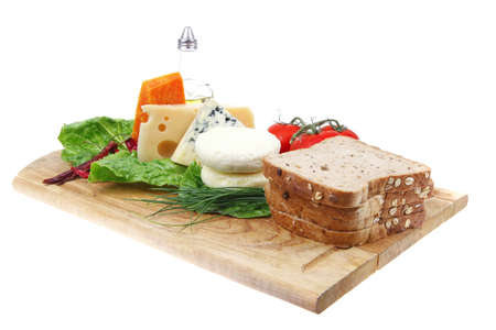 fresh aged french cheeses chops on big cutting board with tomatoes olive oil, rye breadm and green chives isolated over white background Stock Photo - 10738123
