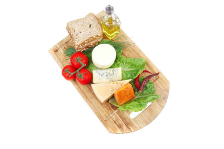 delicatessen cheeses on wooden board with vegetables olive oil and bread isolated over white background Stock Photo - 10738075