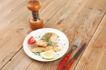 savory sea fish entree : roasted salmon fillet with green onion, red cherry tomatoes pieces, glass pepper grinder, rosemary twigs and lemon on wooden board photo