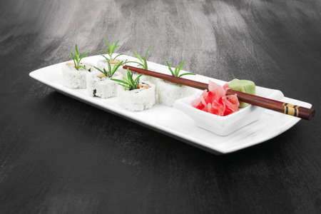 Maki Sushi - California Roll made of Smoked salmon, Cream Cheese and Deep Fried Vegetables inside. With wasabi and ginger. on black table Stock Photo - 10752399