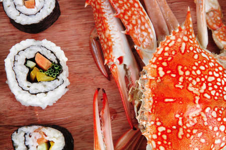 sake maki: Maki Roll with Deep Fried Vegetables inside . on wooden plate with live crab . isolated over white background . Japanese Cuisine  Stock Photo