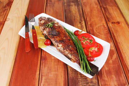 sunfish: served main course on wood: whole fried seabass on plate with lemons,tomatoes and peppers Stock Photo