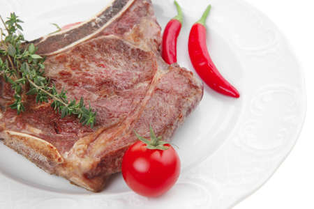 savory : grilled spare rib on white dish with thyme pepper and tomato isolated over white background photo